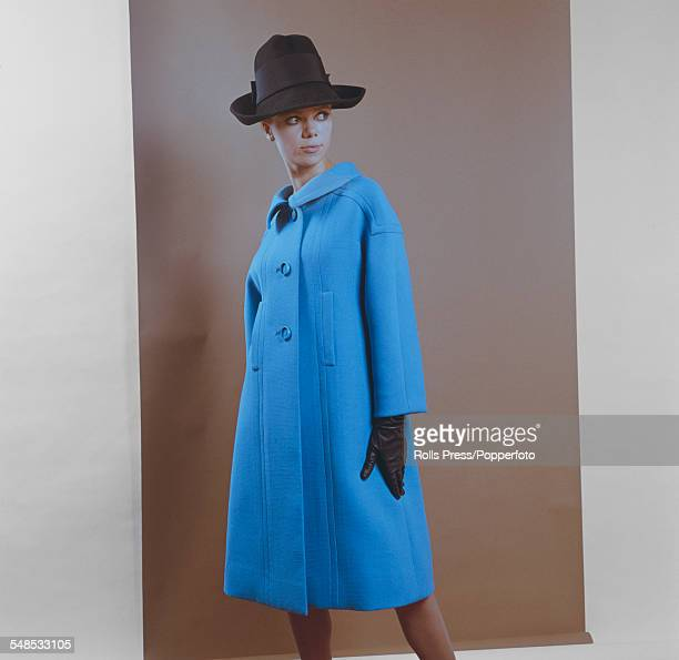 A young female model wears a light blue woollen coat with three buttons on the front two vertical slit pockets small flap collar drooping...