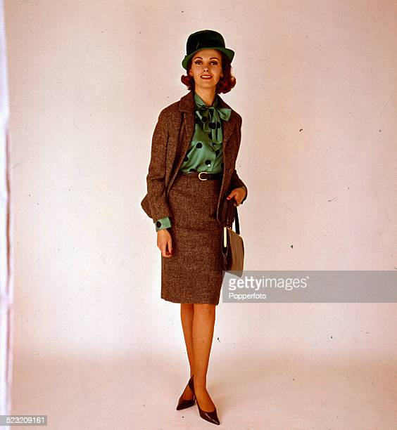 Sixties Fashion - A young female model wears a light brown tweed skirt suit over a green and black polka dot satin style blouse with pussy bow circa...