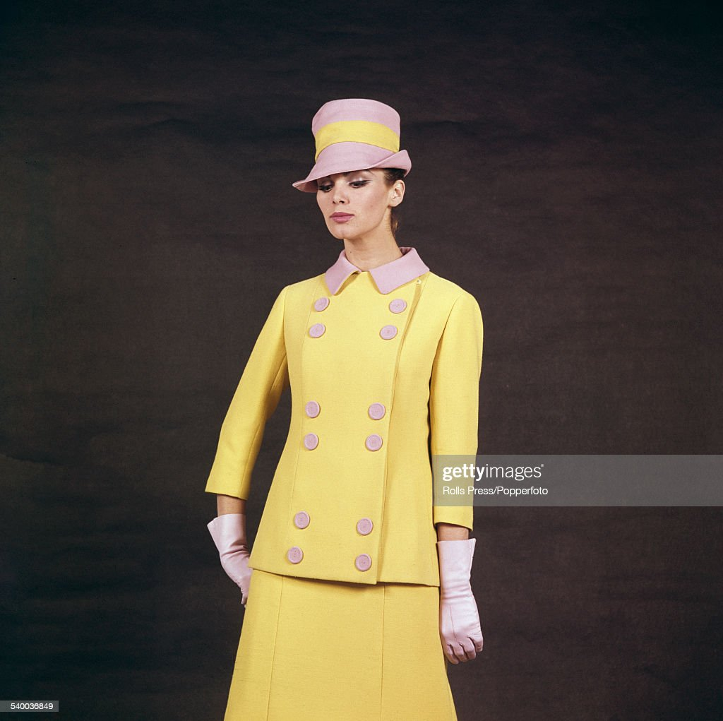 Sixties Fashion - A young female model wears a matching dress and jacket in yellow crepelle with pink collar and twelve buttons on the double breasted front and a yellow band on the matching pink high hat, designed by Germana Marucelli of Milan for the fashion house's Spring/Summer collection in February 1964.