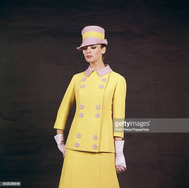 Sixties Fashion A young female model wears a matching dress and jacket in yellow crepelle with pink collar and twelve buttons on the double breasted...