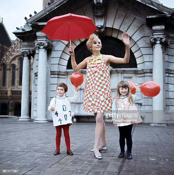Sixties Fashion - A young female model wears a paper dress with a geometric pattern by French fashion designer Paco Rabanne alongside two girls...