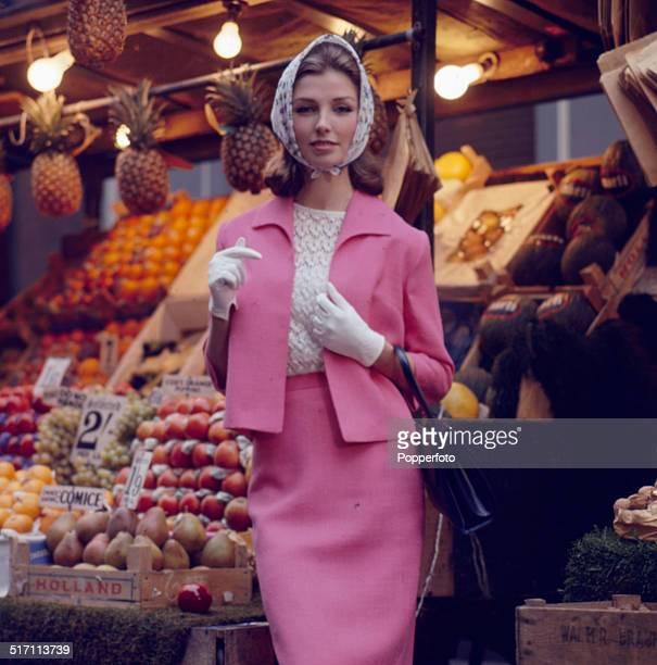 Sixties Fashion - A young female model wears a pink skirt suit over a white blouse and matching head scarf and white gloves whilst standing in front...
