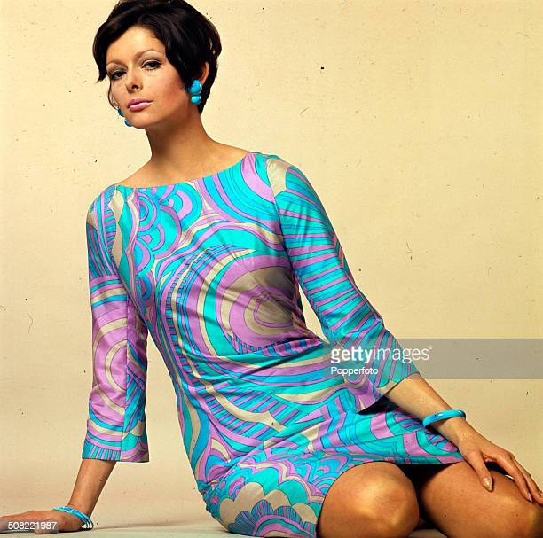 Sixties Fashion - A young female model wears a Pucci style blue and pink patterned mini dress with matching earings circa 1966.