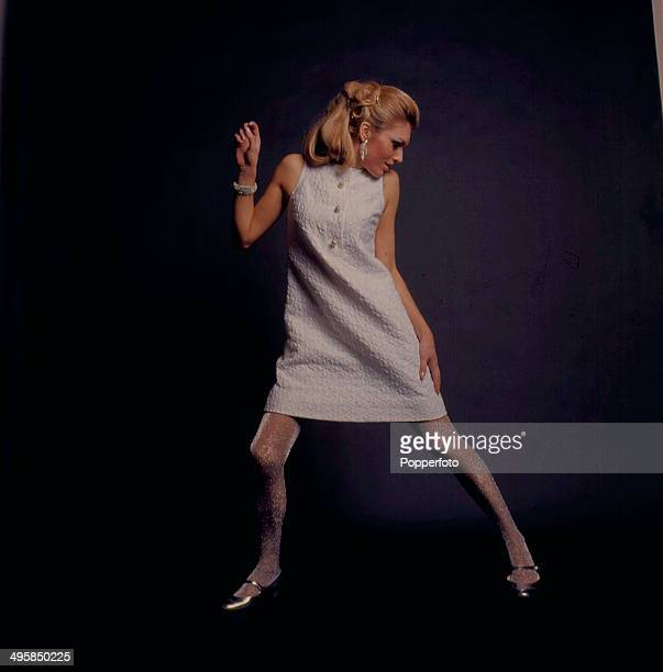 Sixties Fashion A young female model wears a white mini dress and metallic tights and shoes in 1967