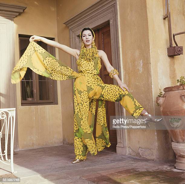 Sixties Fashion A young female model wears matching bodice and chiffon pants in a large floral pattern of yellow on olive green with attached...