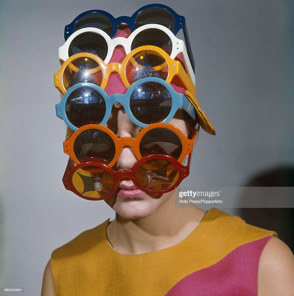Sixties Fashion - a young female model wears multiple versions of differently coloured sunglasses on her head to cover her face and forehead and pink hat in 1967.