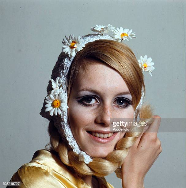 Sixties Fashion A young female model with her hair tied in a plait wears a white knitted bonnet with daisy decoration
