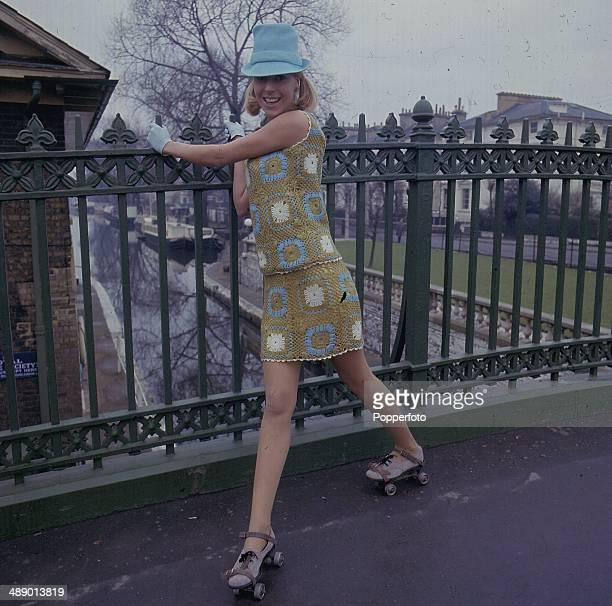Sixties Fashion A young model wears a crochet knit top and matching skirt whilst roller skating on a bridge over a canal in 1967