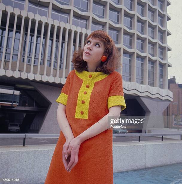 Sixties Fashion A young woman wearing an orange and yellow towelling shift dress with contrast placket and sleeve edges stands in front of the Centre...