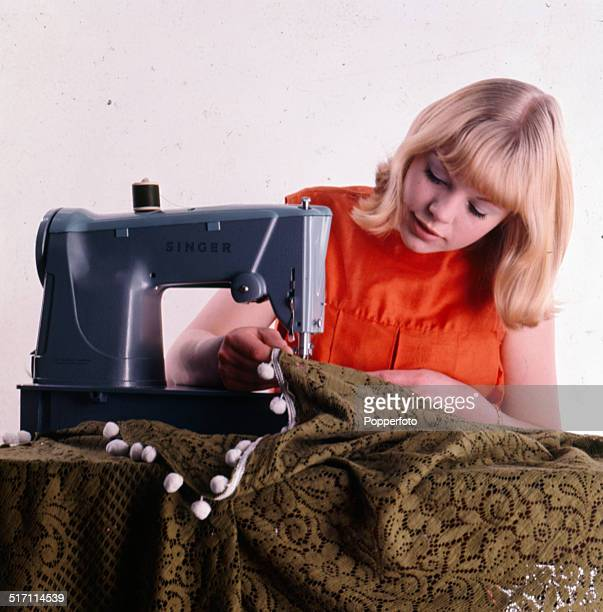 Sixties Fashion A young woman wearing an orange sleeveless top operates a Singer sewing machine to attach a pompom trim to a lace style bedspread...