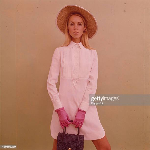 Sixties Fashion A young woman wears a pale pink button up shirt dress with a sun hat pink gloves and handbag in 1968