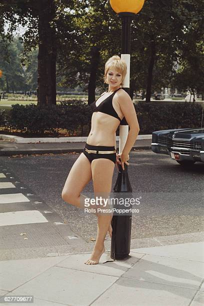 Sixties Fashion British model Mandy RiceDavies poses wearing a black bikini swimsuit with gold belt designed and manufactured by Gottex in Grosvenor...