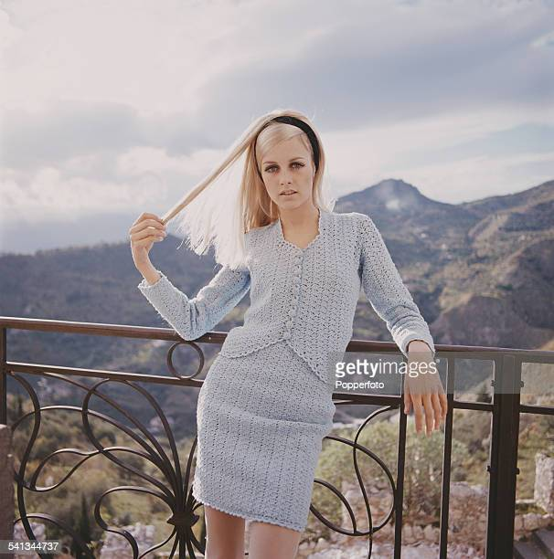 Sixties Fashion English model Twiggy wears a baby blue knitted two piece skirt and cardigan whilst leaning against railings in a Mediterranean...