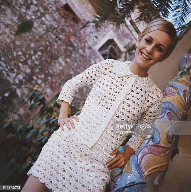 Sixties Fashion English model Twiggy wears a knitted warm glow summer button up jumper and matching short skirt in a Mediterranean setting circa 1967