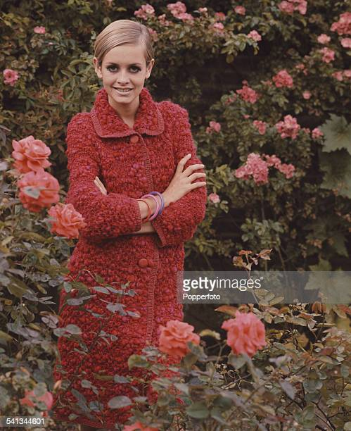Sixties Fashion English model Twiggy wears a red knee length woollen coat in a rose garden circa 1967