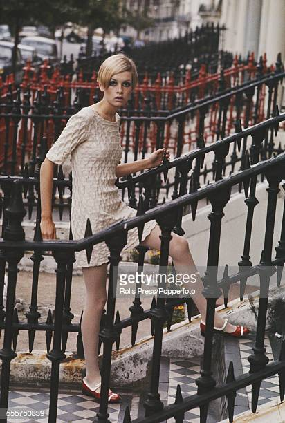 Sixties Fashion English model Twiggy wears a textured cream coloured mini dress whilst standing on steps next to cast iron railings in Ladbroke Grove...
