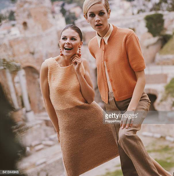 Sixties Fashion English model Twiggy wears an orange knit cardigan over a cream coloured blouse with casual loose fit trousers beside another young...