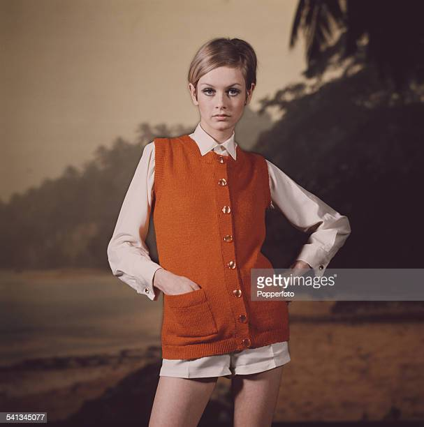 Sixties Fashion English model Twiggy wears an orange knitted sleeveless cardigan over a cream coloured shirt and shorts in front of a beach scene...