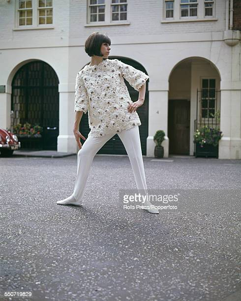 Sixties Fashion model Rosemary Wilkins wears an outfit in white lace with tan motif ski top and white stirrup pants designed by Swiss born fashion...