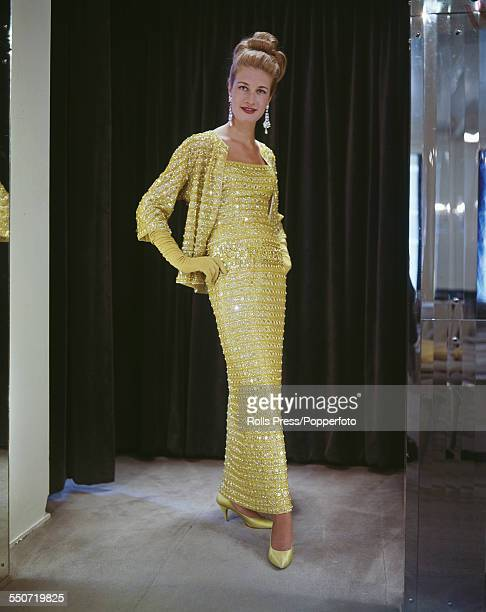 Sixties Fashion - model Sally Jamieson wears 'Limey', a full length figure hugging evening dress embroidered with diamonds, silver and crystal...