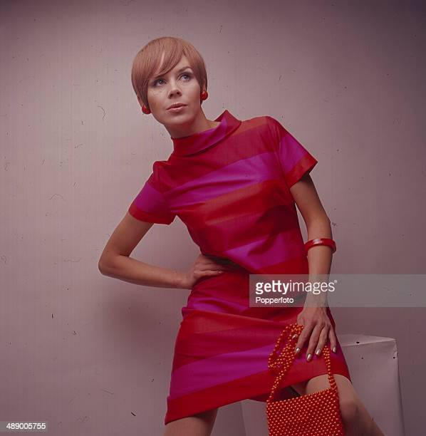 Sixties Fashion Portrait of a young woman wearing a pink orange and red striped funnel neck mini shift dress and holding a red beaded handbag circa...