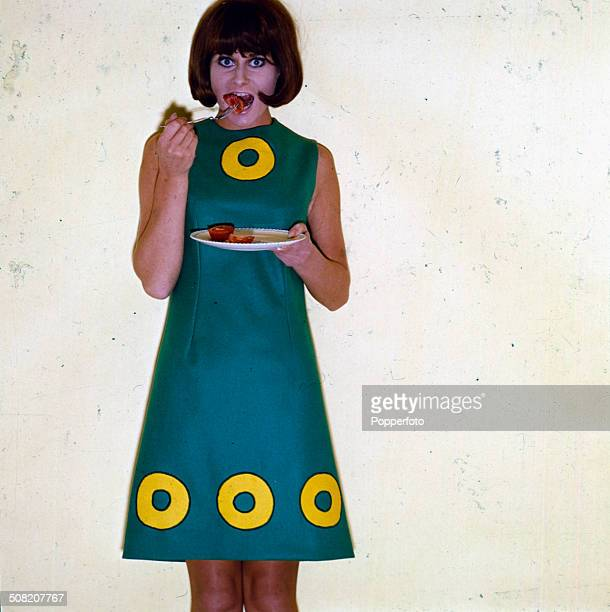 Sixties Fashion Studio photo shoot of a young female model wearing a blue/turquoise knee length sleeveless Aline shift dress with a yellow circle...