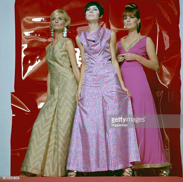Sixties Fashion Three young female models pose wearing full length party dresses in pink and gold in front of a shiny red back drop circa 1966