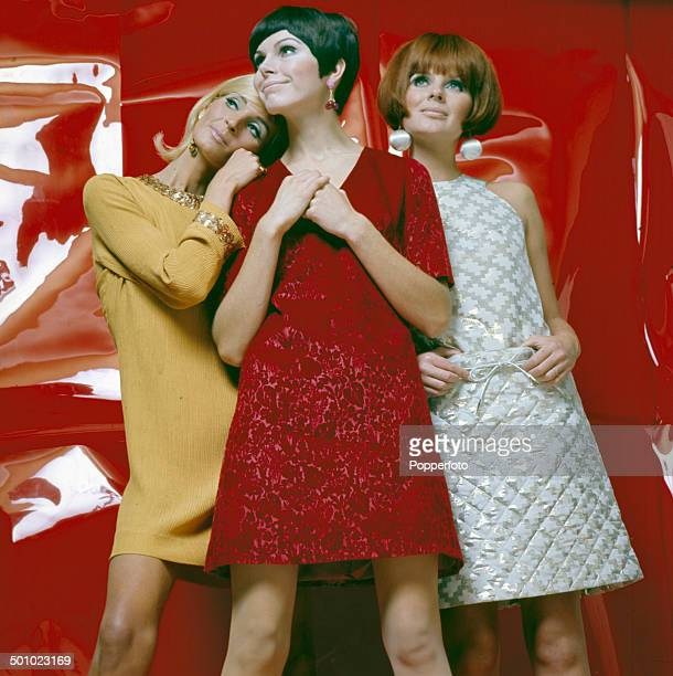 Sixties Fashion Three young female models pose wearing party dresses in white red and yellow in front of a shiny red back drop circa 1966