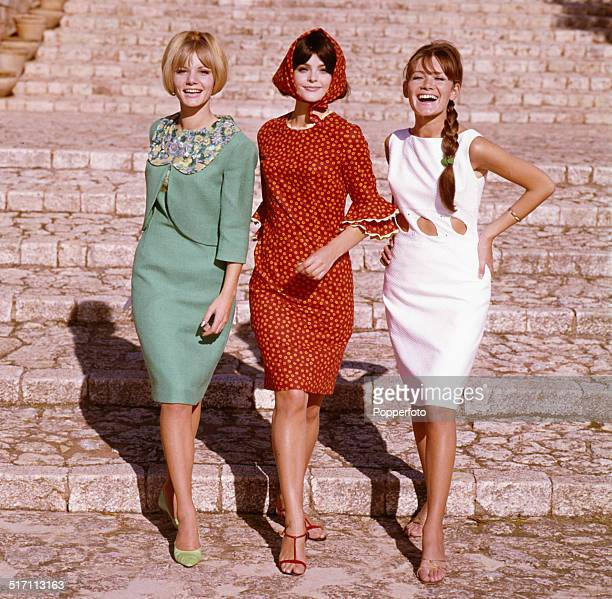 Sixties Fashion Three young female models two wearing knee length summer dresses and the other wearing a two piece dress and summer jacket walk down...