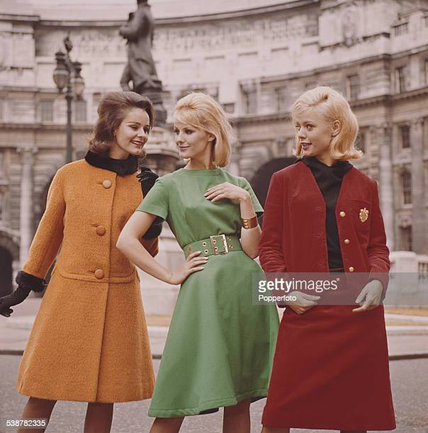 Sixties Fashion Three young female models wearing from left an orange princess coat a green dress and a red jacket and matching skirt pose in front...