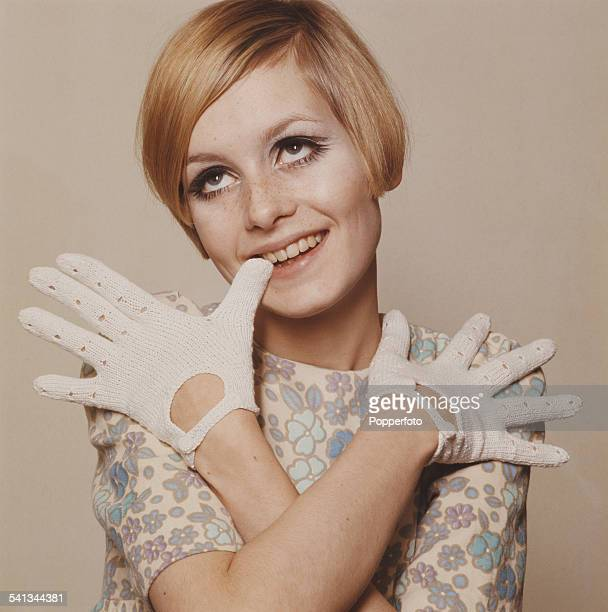 Sixties Fashion Twiggy models a cream summer dress with blue flower motif and white knitted gloves circa 1966