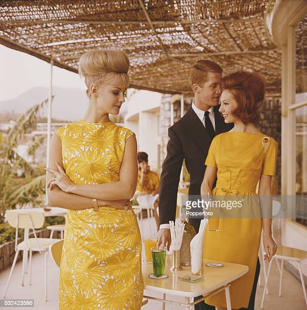 Sixties Fashion Two young female models one wearing a yellow sleeveless summer dress with a flower print motif and the other wearing a yellow fitted...