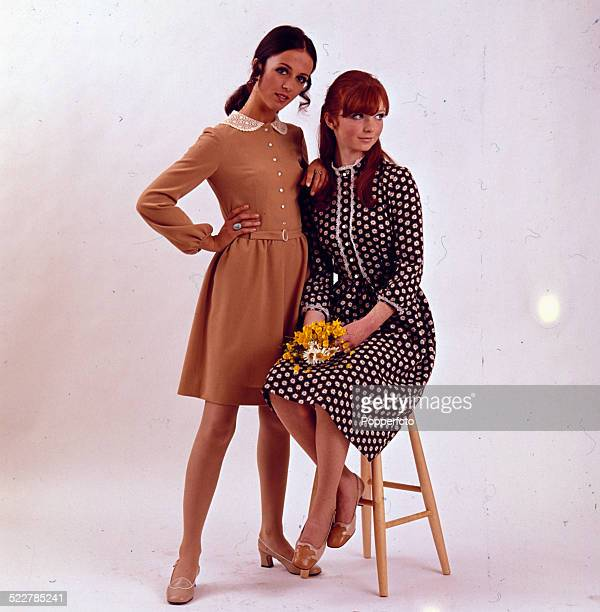 Sixties Fashion Two young female models pose in a studio with one wearing a light brown over the knee dress with peter pan collar and the other...