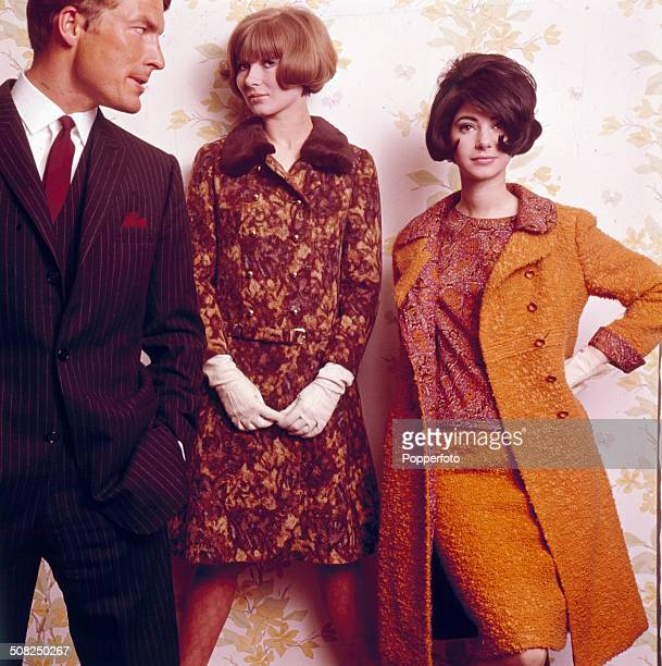 Sixties Fashion Two young female models pose one wearing matching jacket and skirt with floral pattern and fake fur collar and the other wearing...