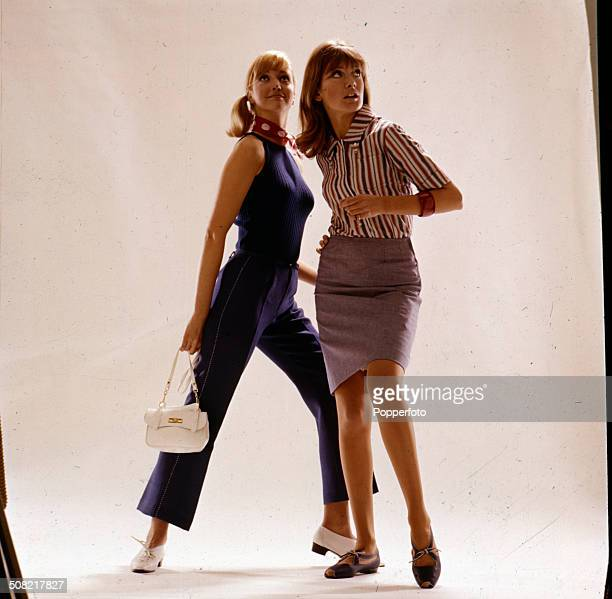 Sixties Fashion Two young female models pose with one wearing a striped shirt and knee length skirt and the other in a knitted ribbed blue sleeveless...