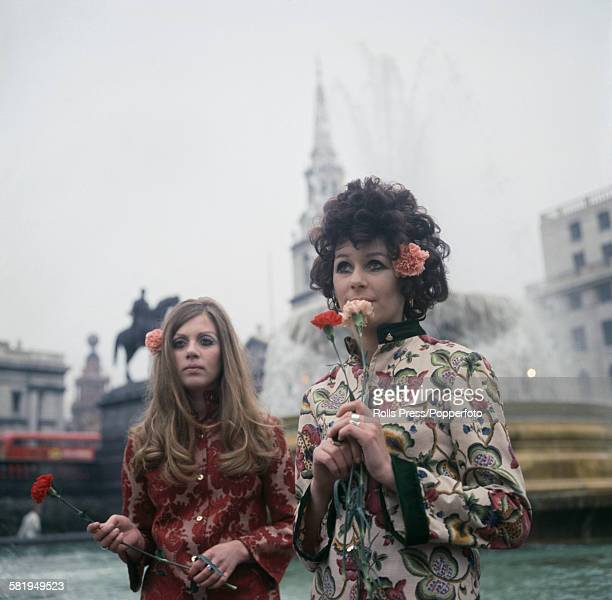 Sixties Fashion two young girls dressed in floral print hippie style tunics stand holding flowers in Trafalgar Square London in November 1967