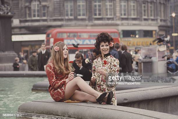 Sixties Fashion two young girls dressed in floral print hippie style tunics stand holding flowers beside ornamental fountains in Trafalgar Square...