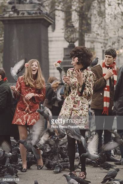 Sixties Fashion two young girls dressed in short floral brocadeprint coats stand holding flowers as pigeons fly around them in Trafalgar Square...