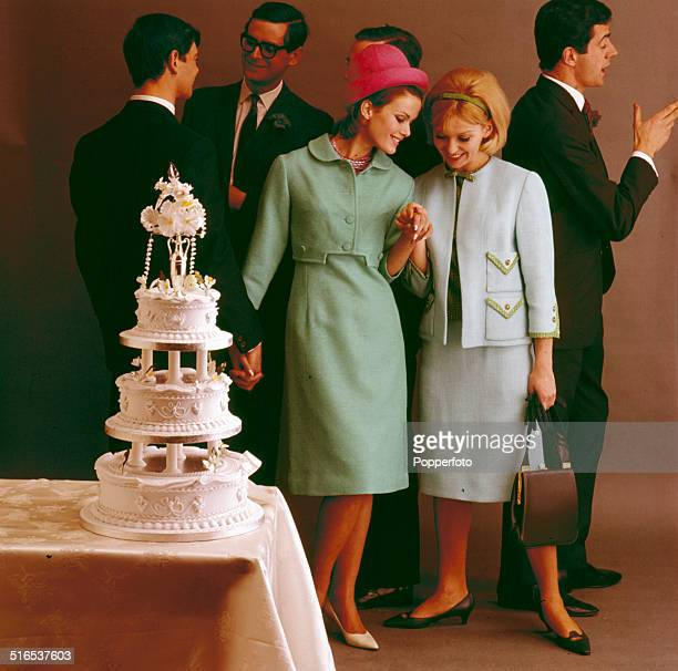 Sixties Fashion Two young women pose wearing jacket and skirt suits in a wedding scene with a tiered wedding cake circa 1964