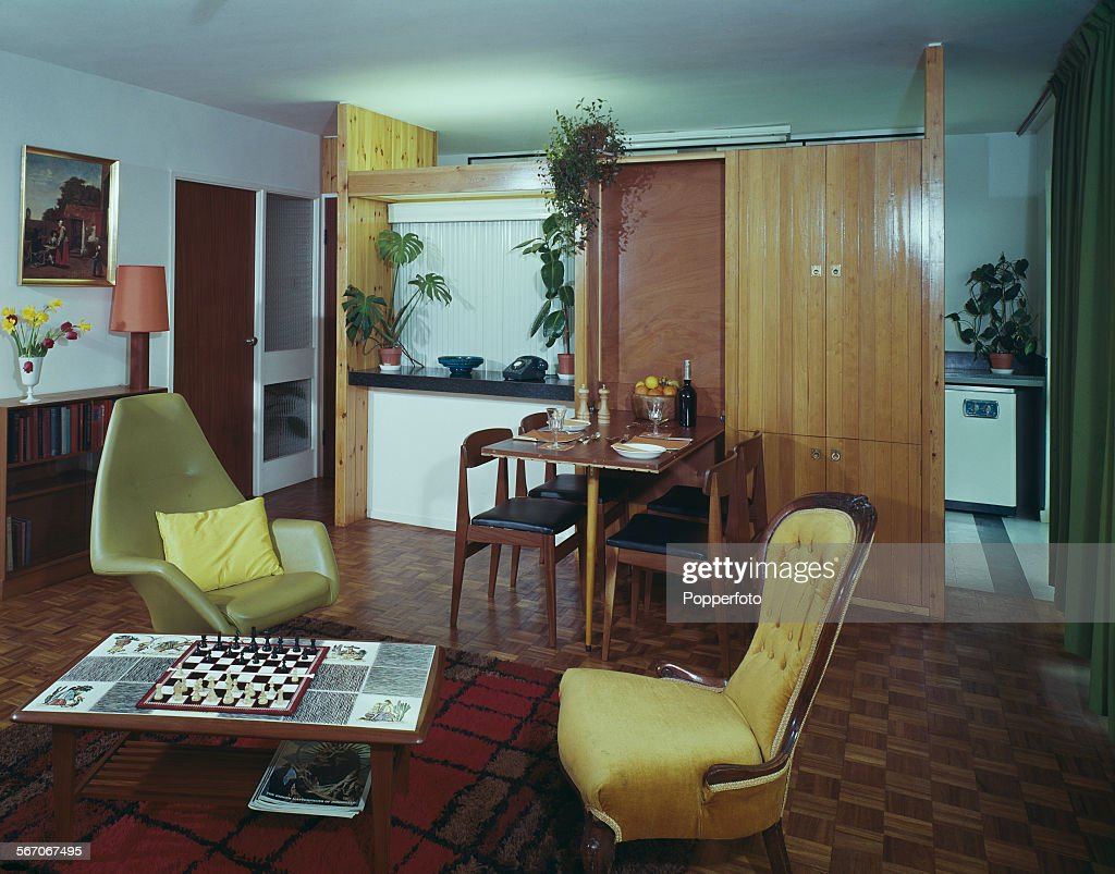 Sixties Interior Design - View of the interior living room and dining area of a modern flat, featuring a swivel chair and vintage georgian style chair with tile covered coffee table standing on a contemporary rug with dining table and chairs behind and kitchen just visible but partially hidden by wooden storage area and screen in an English home in 1967.