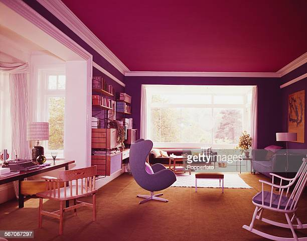 Sixties Interior Design View of the interior living room area featuring a swivel lounge chair sofas a desk with typewriter and wall mounted...