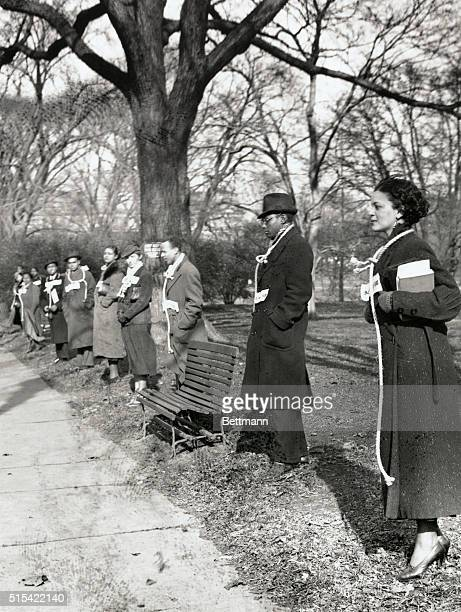 Sixty or more black picketers from Memorial Continental Hall on 17th St wear strands of rope around their necks to protest omission of lynching in...