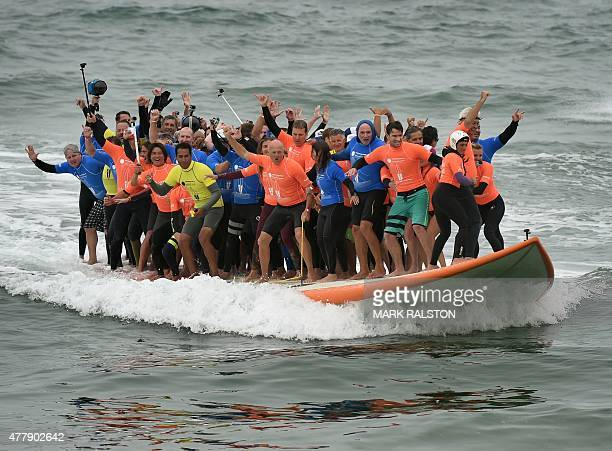 Sixty six surfers from Huntington Beach ride the world's largest surfboard as they break the 'Guinness Book of Records' record for the largest number...