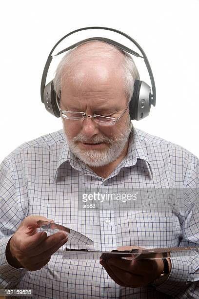 Sixty year old man listening to music through headphones