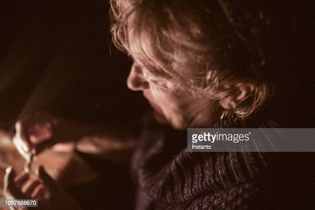 sixty year old woman rolling a joint of cannabis, prescribed medecine for chronic illness. - dependency stock pictures, royalty-free photos & images