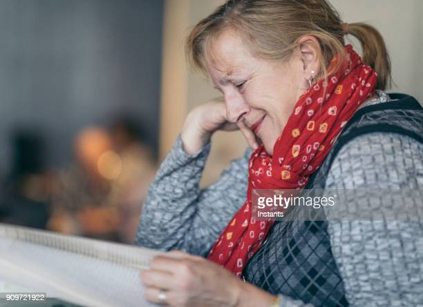 sixty year old woman who finds her book funny, while reading in a café. - 63 year old female stock pictures, royalty-free photos & images