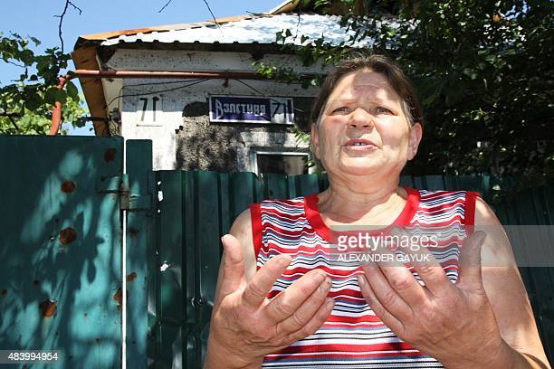 Sixty yearold pensioner Galina speaks to journalists in front of her house near to the airport in Donetsk on August 2 2015 She and her sister refuse...