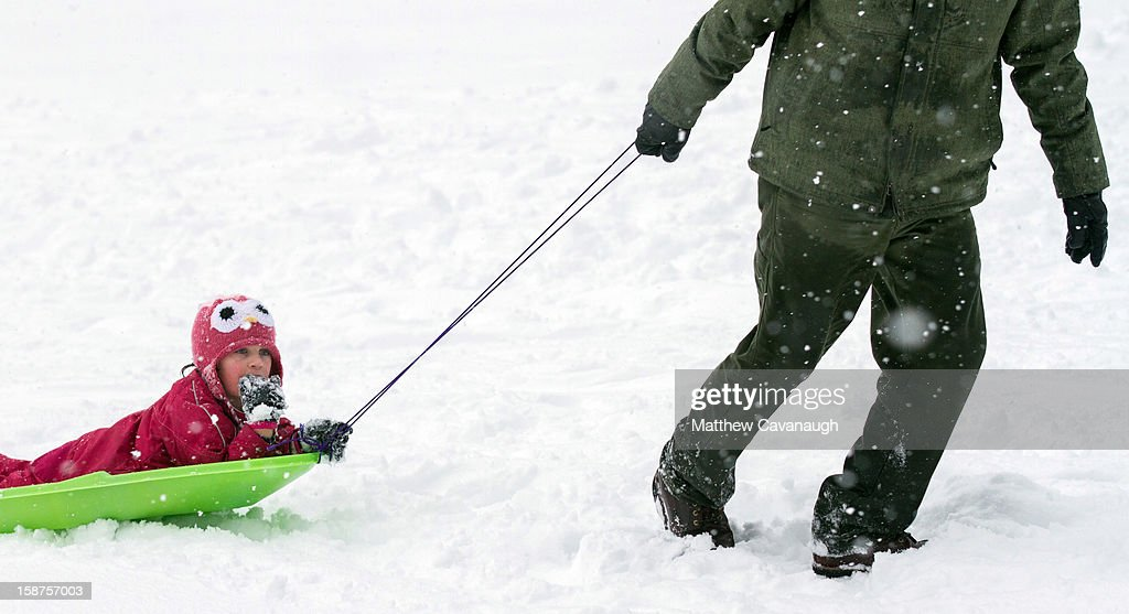 Six-year-old Amaya Eddy of Trenton, ME is pulled along on a sled by her father on December 27, 2012 in Greenfield, Massachusetts. A serious winter storm that caused tornados in the South on Christmas Day swept across the Northeast on Thursday, bringing snow, sleet, rain and causing dangerous travel conditions.