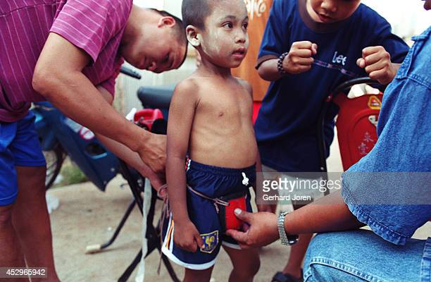 A sixyearold boxer has help from his father and an older boxer in how to wear a metal cup before a fight at an amusement park in Mae Sot In the...