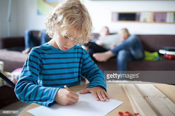 Sixyearold boy drawing a picture in the background mother and brothers on August 05 in Sankt Augustin Germany Photo by Ute Grabowsky/Photothek via...